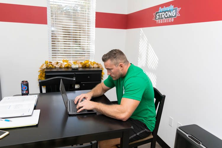 personal trainer keith hansen displaying poor posture while hunched over a computer