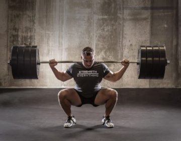 Personal Trainer Keith Hansen in the bottom of a 405lb high bar squat wearing a strength over everything shirt