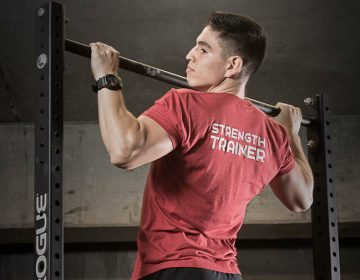 Personal Trainer Gustavo Ramos performing a pull up wearing a strength trainer shirt