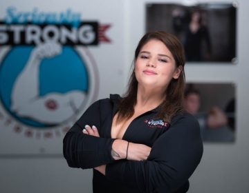 Athena Landy, a personal trainer at seriously strong training gym, folding her arms across her chest for a professional headshot