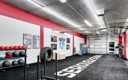 "A View of Tallahassee's personal training gym featuring black turf that says ""Seriously Strong"" across the length"