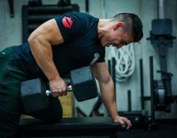 a personal trainer at seriously strong training gym performing heavy dumbbell rows