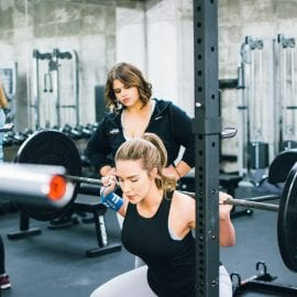 A young female performing a low bar squat while being coached by a personal trainer at seriously strong training's personal training gym