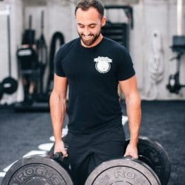 a personal trainer at seriously strong training performing farmers walks in the gym